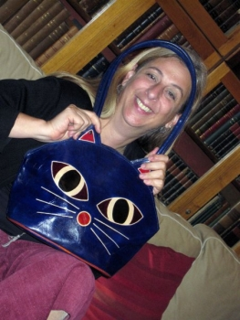 Eleni Calligas holds a purse with a cat face, showing her love of felines