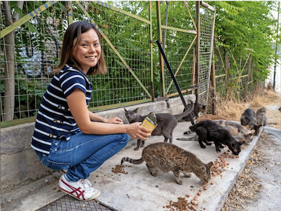 Nine Lives volunteer feeds the cats on her normal route while giving a cat tour of Athens
