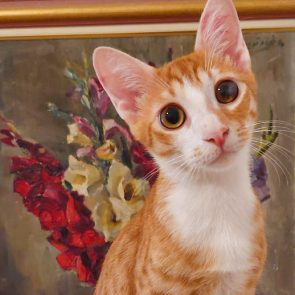 One of two rescued kittens sitting in front of a painting of flowers
