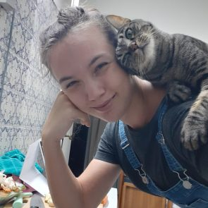 A unique tabby cat is rubbing her head against her foster mum while sitting on her shoulder.